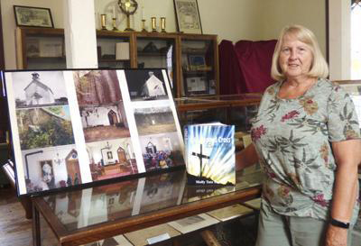 Molly Shaffer stands in the museum at The Old Rugged Cross Church in Pokagon next to pictures of the church and her new book.